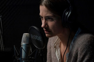 Woman speaking into audio studio microphone