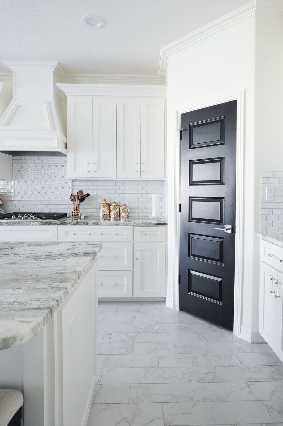 A gorgeous and bright white kitchen with shaker cabinets, fantasy brown granite and a stunning black pantry door. I LOVE the backsplash!