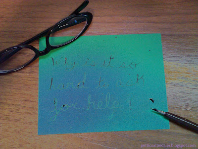 Note sized piece of green card stock reads: Why is it so hard to ask for help? The text is written with black ink from a dip pen which sits dripping in the bottom right hand side of the image.  In the top left side of the image are a folded up pair of black glasses that overlap the corner of the card stock.  The whole image is obscured as though the sun is washing it out.
