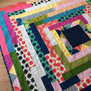 bright quilt, with square centre and jelly roll strips