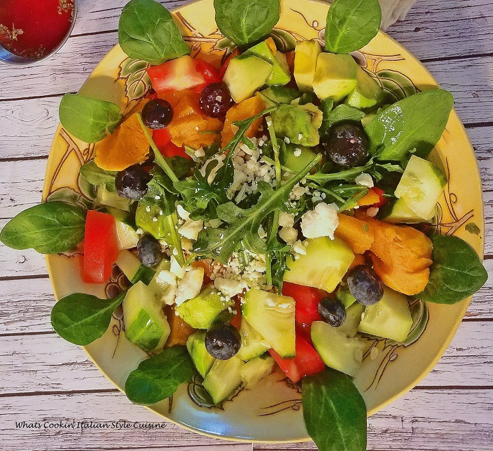 this is roasted butternut squash in a salad with arugula, blueberry, avocado and cucumbers, tomatoes and much more