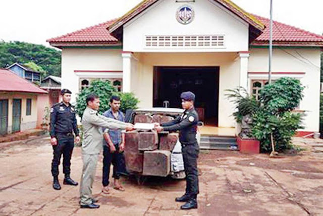 Military police hand over a suspected timber transporter and a load of luxury timber to Forestry Administration officials in Kratie province. Photo supplied