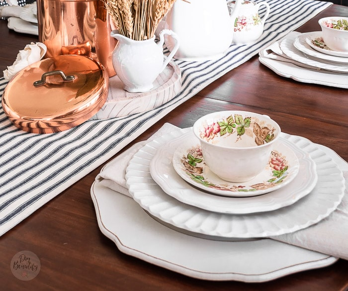 dining table with striped runner, thrifted vintage teacups, layered place settings and copper accents