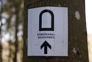 Das Wegzeichen des Römerkanal Wanderwegs. Ein schwarzer querschnitt der Eifelwasserleitung auf weißem Grund.