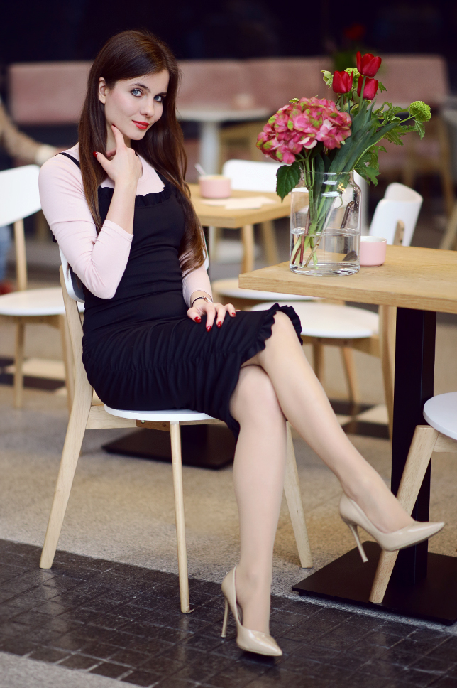 Czarna dopasowana sukienka do kolan, różowa bluzka, cieliste rajstopy i beżowe szpilki