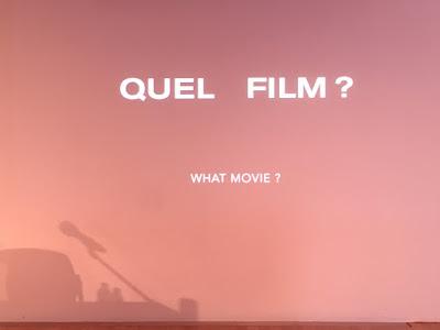 Leinwand mit Rednerpult und Mikrophon als Schatten. Schrift: Quel film?