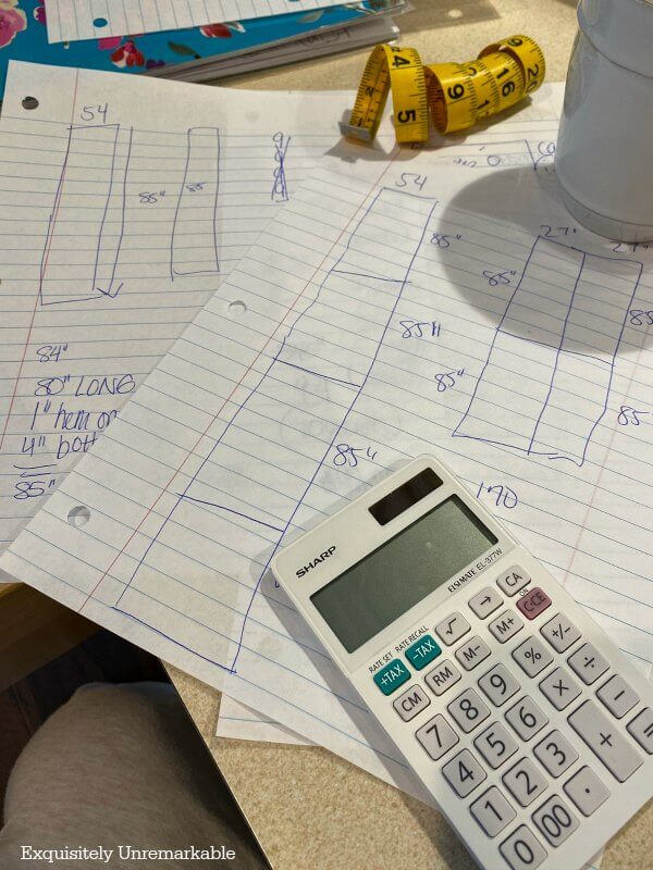 Looseleaf paper with curtain pattern drawings on desk with calculator and measuring tape