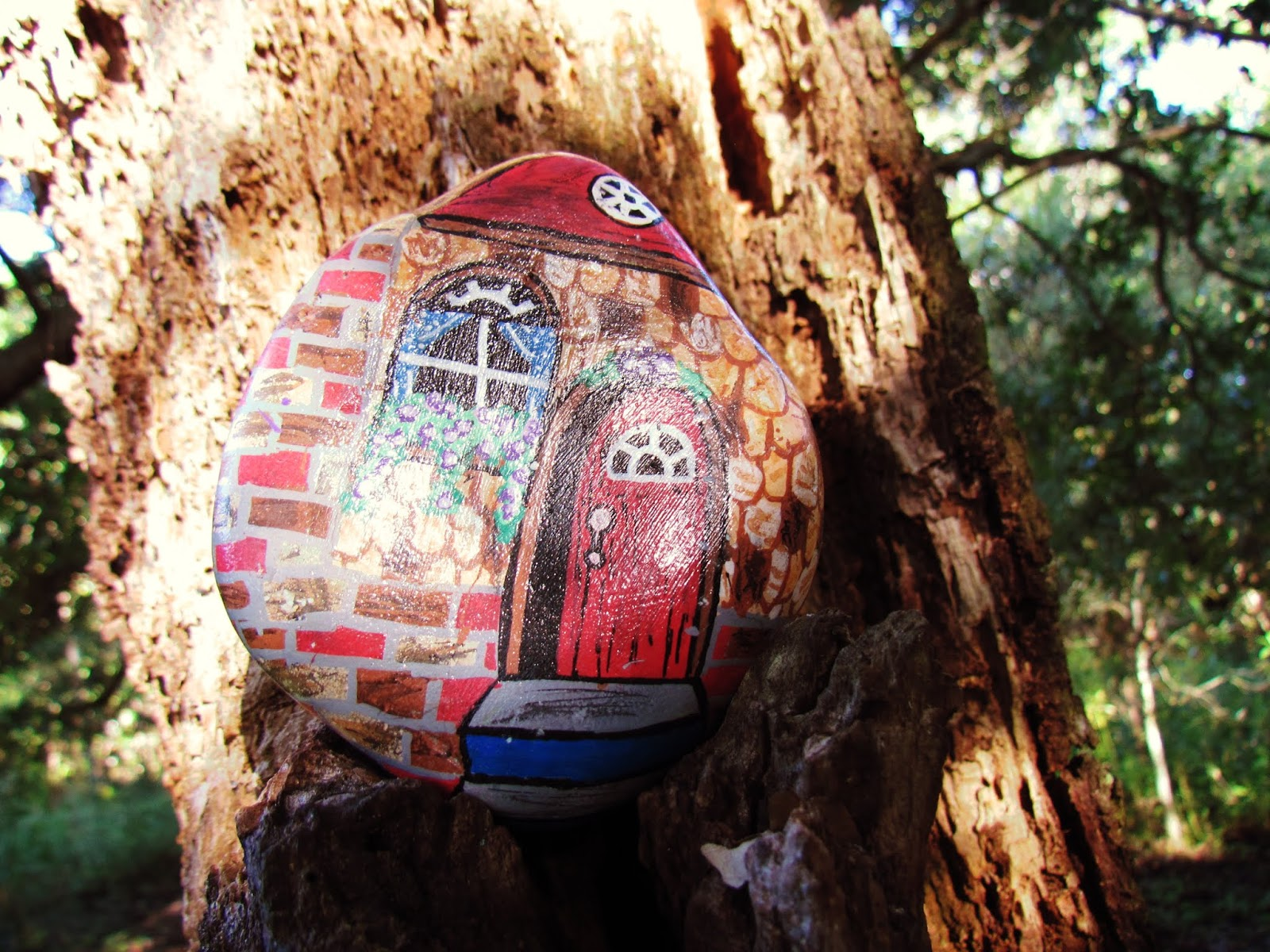 A wooden log holding a painted rock with a picture of a country cottage in the woodland