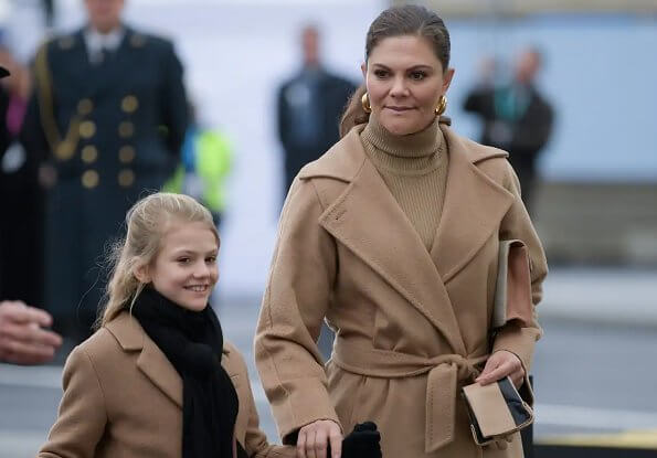 Crown Princess Victoria wore a camel coat by Max Mara, and gold earrings by Sophie by Sophie. Princess Estelle. By Malene Birger clutch
