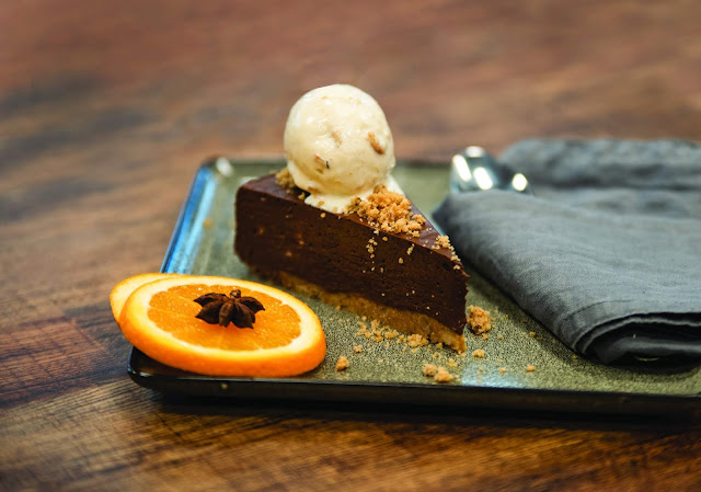 Two slices of orange with cinnamon, a piece of chocolate torte with cream on a square plate with napkin and spoon