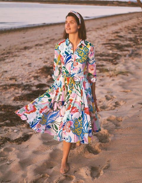 Girl in a colorful shirt dress walking on a beach