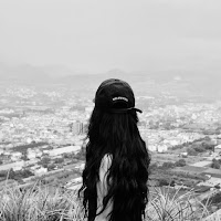 Woman in ball cap with long, dark, wavy hair looking out over a cliff. Only the back of her visible.