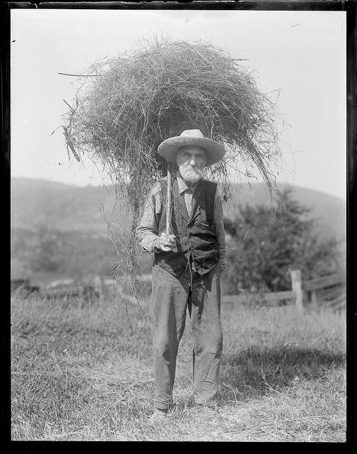 Old black and white photo. An old farmer poses with a bundle of hay on a pitchfork. Speak Your Mind and other stories of Grandmas and reason. marchmatron.com