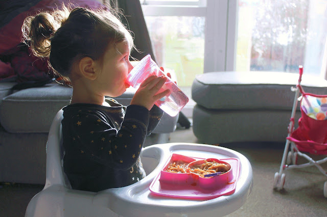 Photograph of a young child in a high chair sipping from a cup with a plate of food in front of them