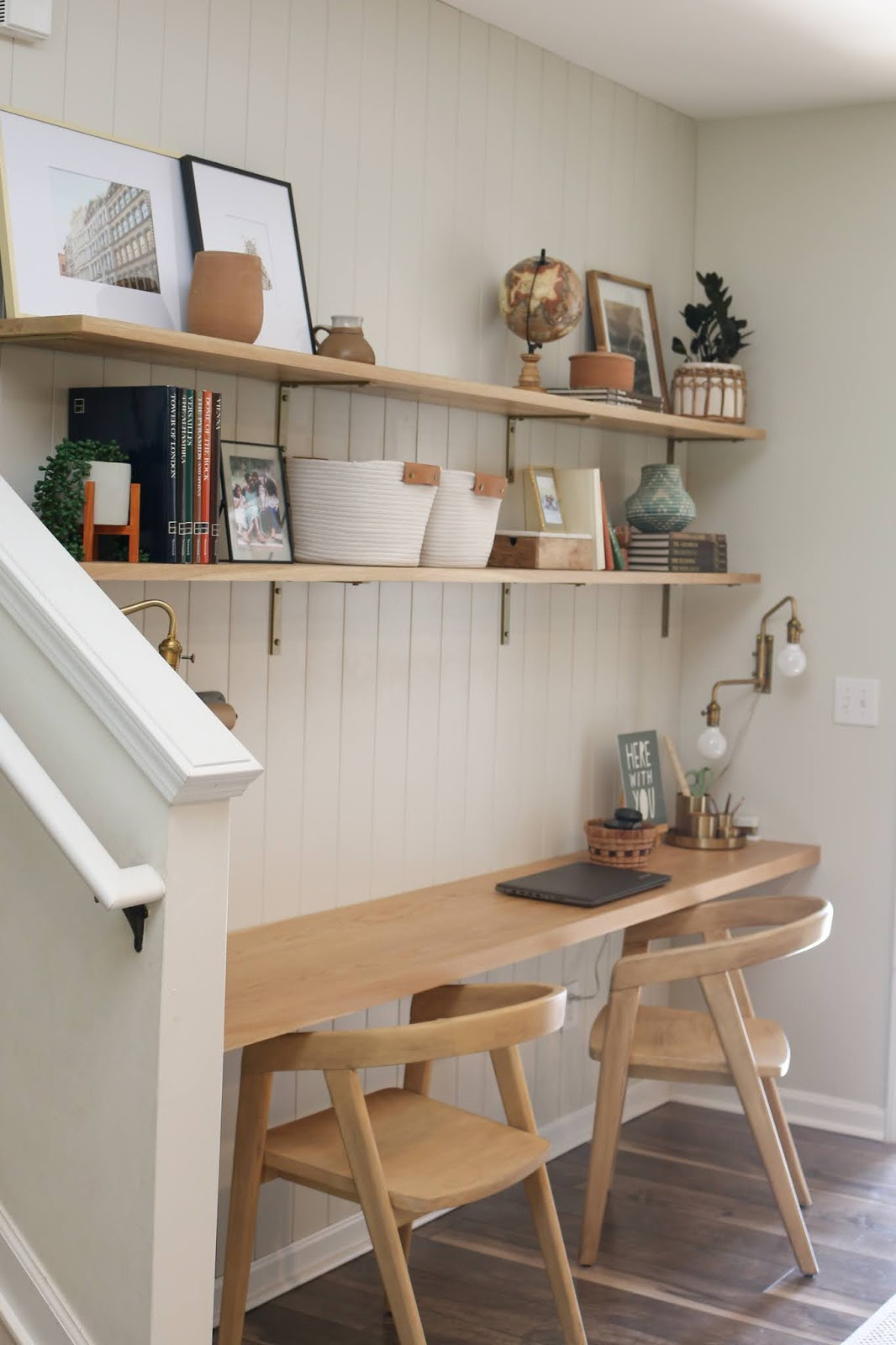 A DIY office nook with built in desk, vertical shiplap, and wall to wall shelves on brackets