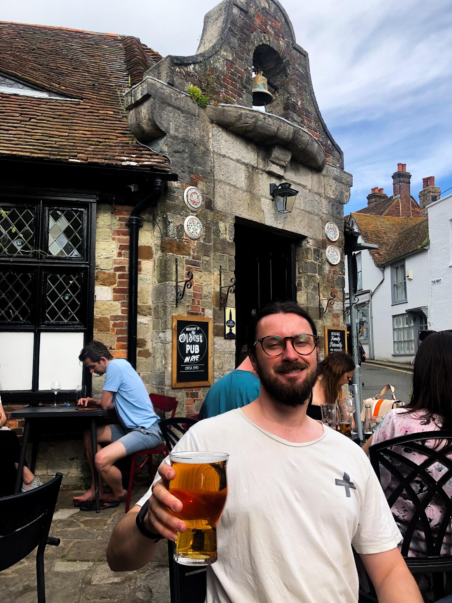 a man holds a pint outside pub