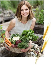 Γυναίκα σε βράχια καθισμένη κρατάει καλάθι με καρότα και διάφορα λαχανικά