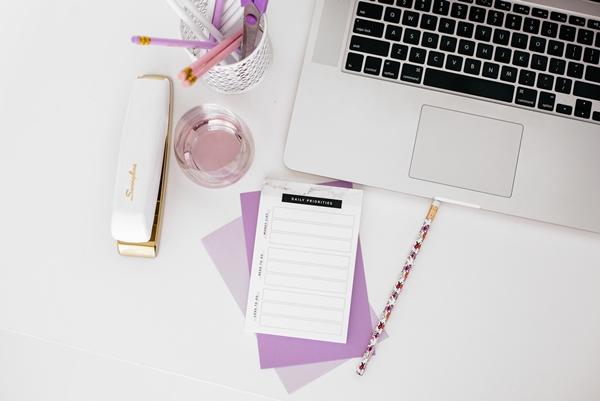 Flatlay home office feminino computador canetas e grampeador