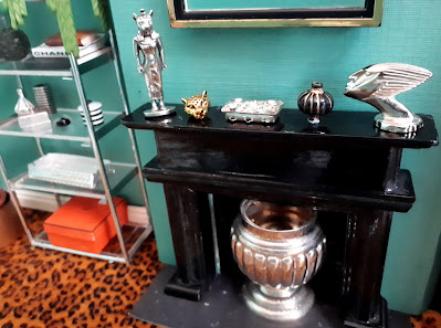 One-twelfth scale modern miniature art-deco inspired room, with a chrome and glass bookshelf next to a fireplace displaying a selection of art-deco ornaments in silver and gold.