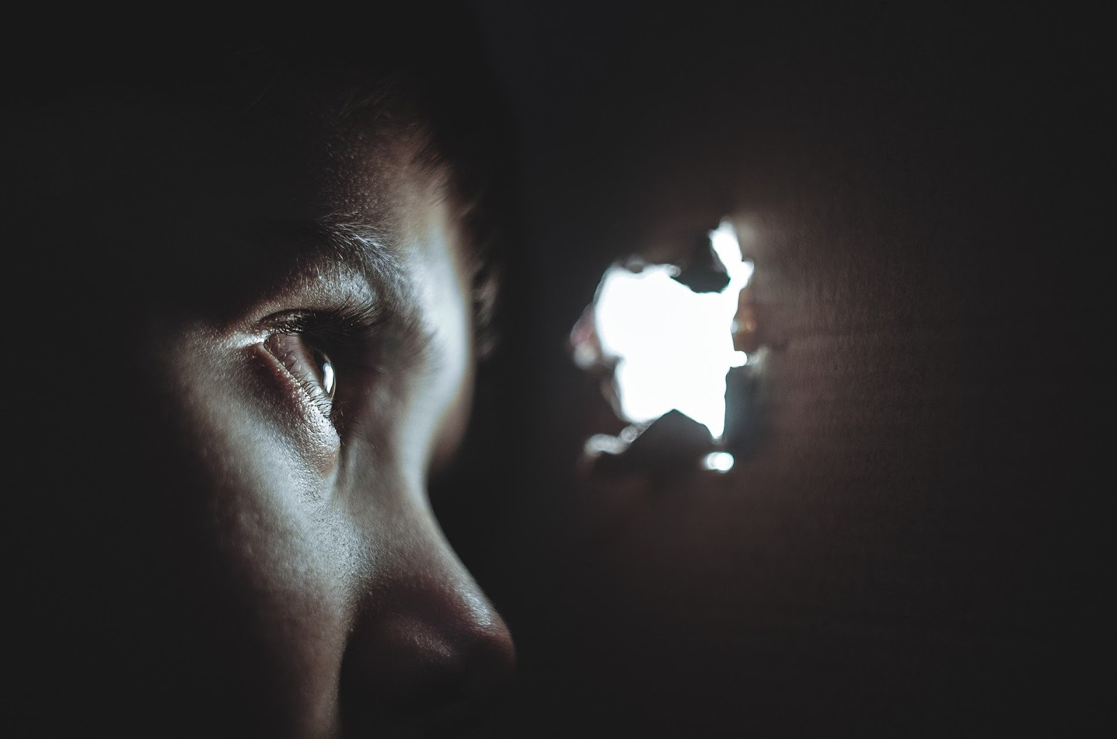 a young child in darkness looking through a hole in the wall to illustrate a blog post about war movies argo and zero dark thirty