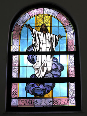 Stained glass window of Jesus rising.