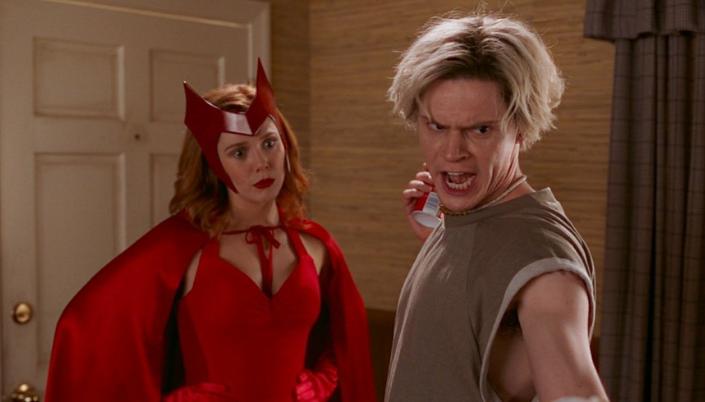 Imagem: Wanda, em sua fantasia de Halloween, com as mãos na cintura e uma expresão aborrecida, ao lado de Pietro, com cabelos brancos, segurando uma latinha de refrigerante, gritando e apontando para baixo.
