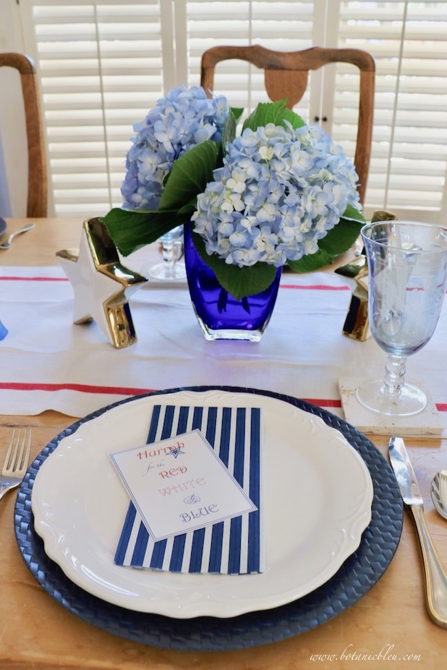 set a stars and stripes patriotic table setting with white plates blue chargers and striped napkins
