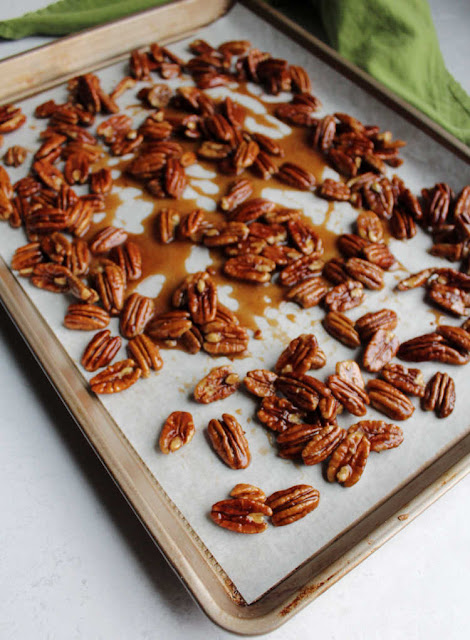 honey coated pecans cooling on parchment paper