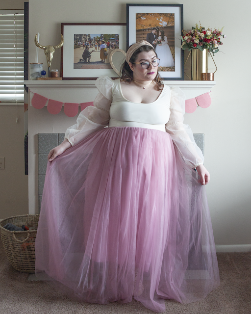 An outfit consisting of lace hedscarf, cream top with puffy organza long sleeves and a pink tulle maxi skirt.