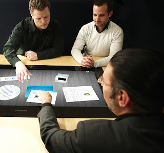 Three people sitting around a digital table exploring documents.