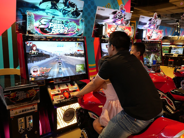 daughter riding a fake motorcycle with father as he plays the Speed Rider 2 video game