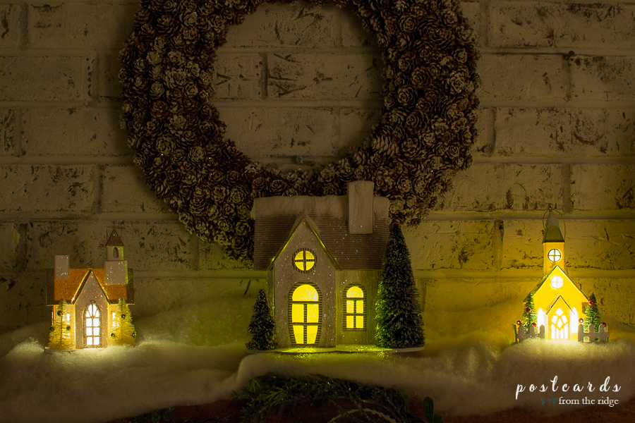 little houses on a mantel lit up at night