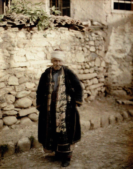An elderly Turk dressed in the traditional Turkish costume consisting of a tunic, waistcoat, trousers, belt, fur coat and fez.