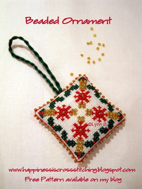 Beaded cross stitch finished into a christmas ornament or scissor fob using gold beads and red and green stranded cotton thread