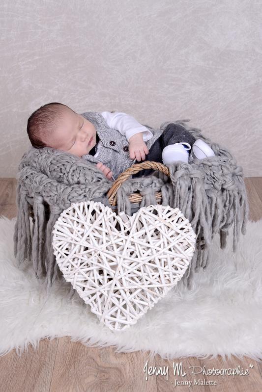 photo bébé allongé dans panier en osier gris avec plaid gris et coeur en osier blanc