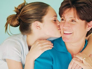 A young teenage girl kissing her mum on the cheek.