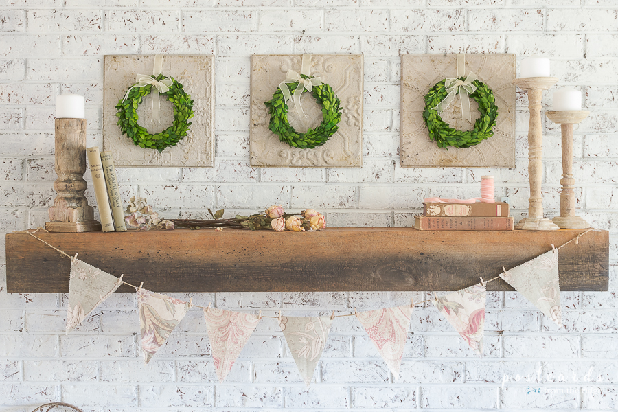 mantel with vintage decor and boxwood wreaths