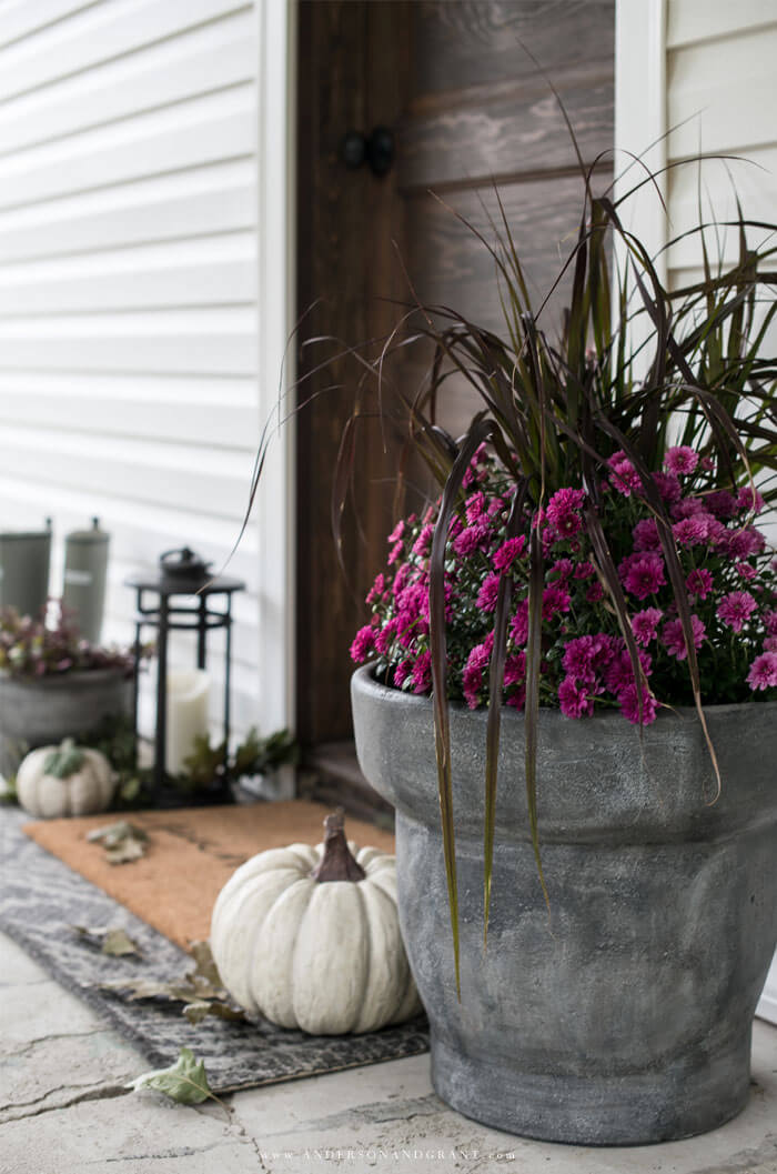See how a farmhouse style front porch is decorated simply with purple mums.