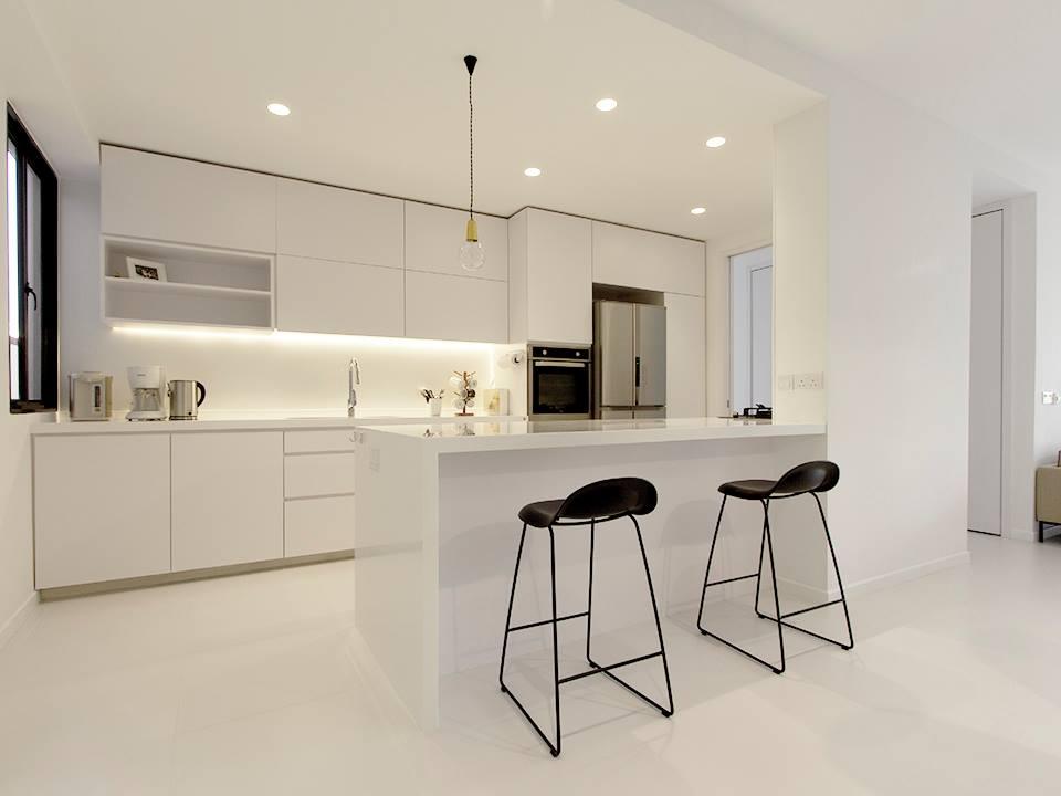 Una cocina blanca abierta y con la placa de coccin