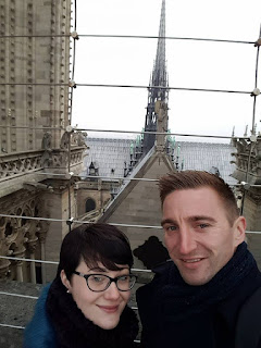 Image of a young couple standing high up in the notre dame cathedral paris france