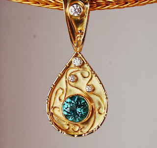 Tear drop shaped pendant with blue stone and diamonds