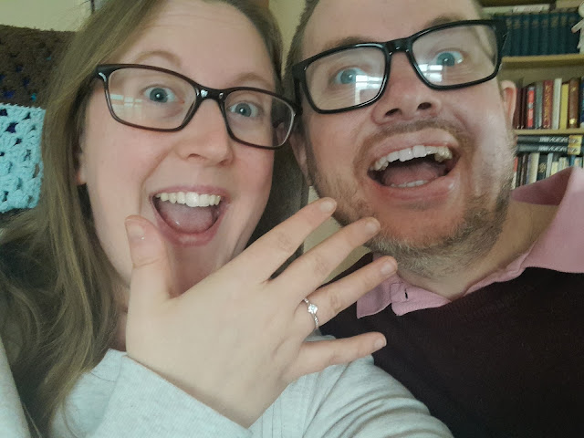 On the left, Hannah a white female holds up her hand with a silver engagement ring on. She has a big smile. Martyn, a white mail sits to her left wearing blog black glasses and smiling with a big grin.