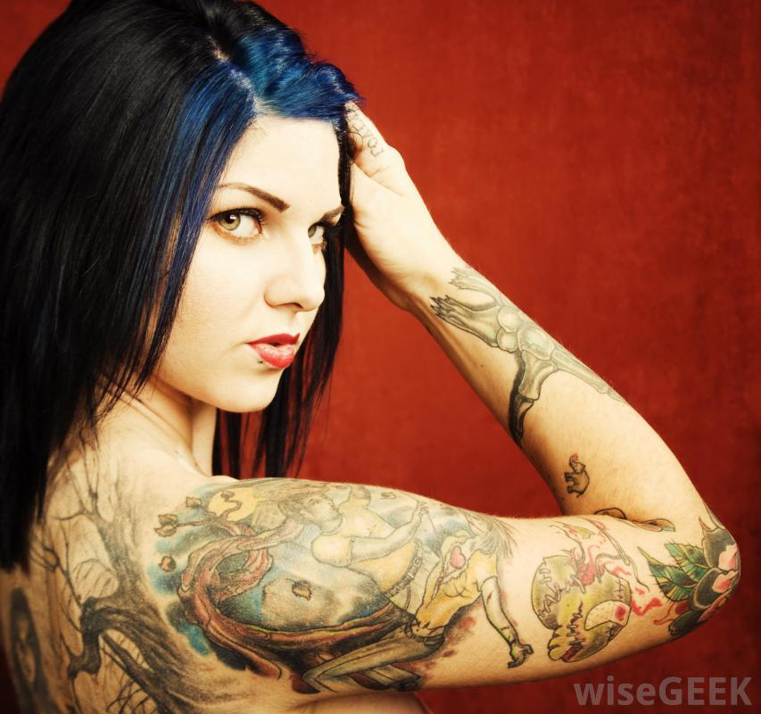 preciosa mujer morena de ojos verdes, se aparta el pelo de la cara, vemos tatuajes en el brazo