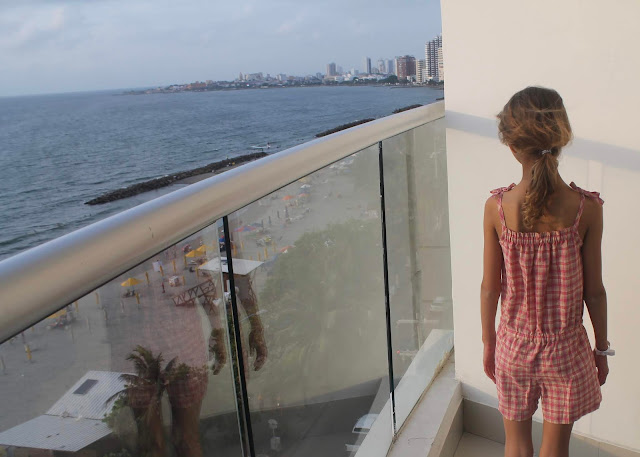 Purl Soho summer romper in pink plaid shirting with a view of the Caribbean.