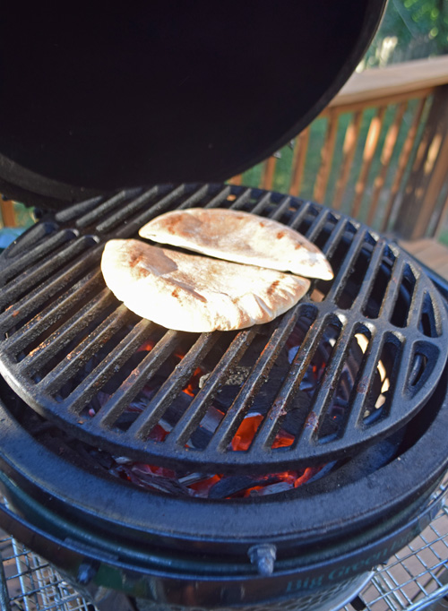 Toasting pita bread over red hot coals on a small kamado grill.