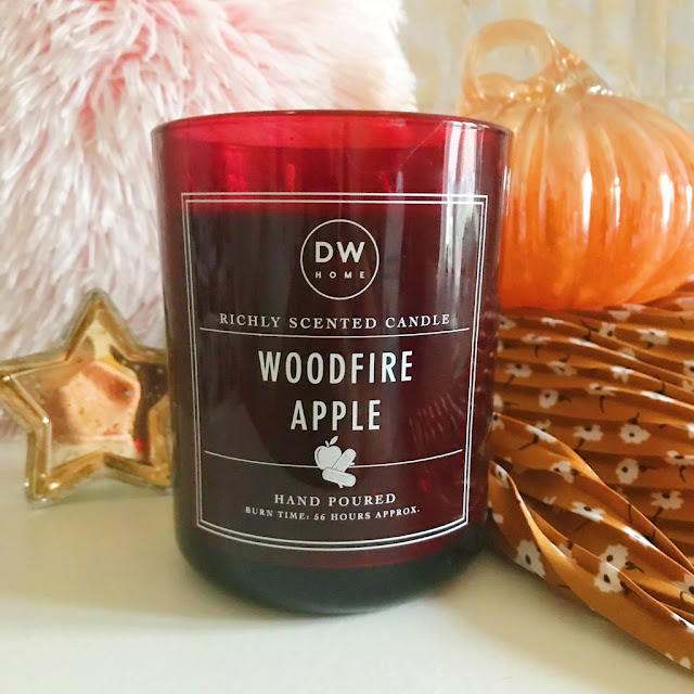 DW Home candle stood up in front of pink fluffy pillow, pumpkin ornament