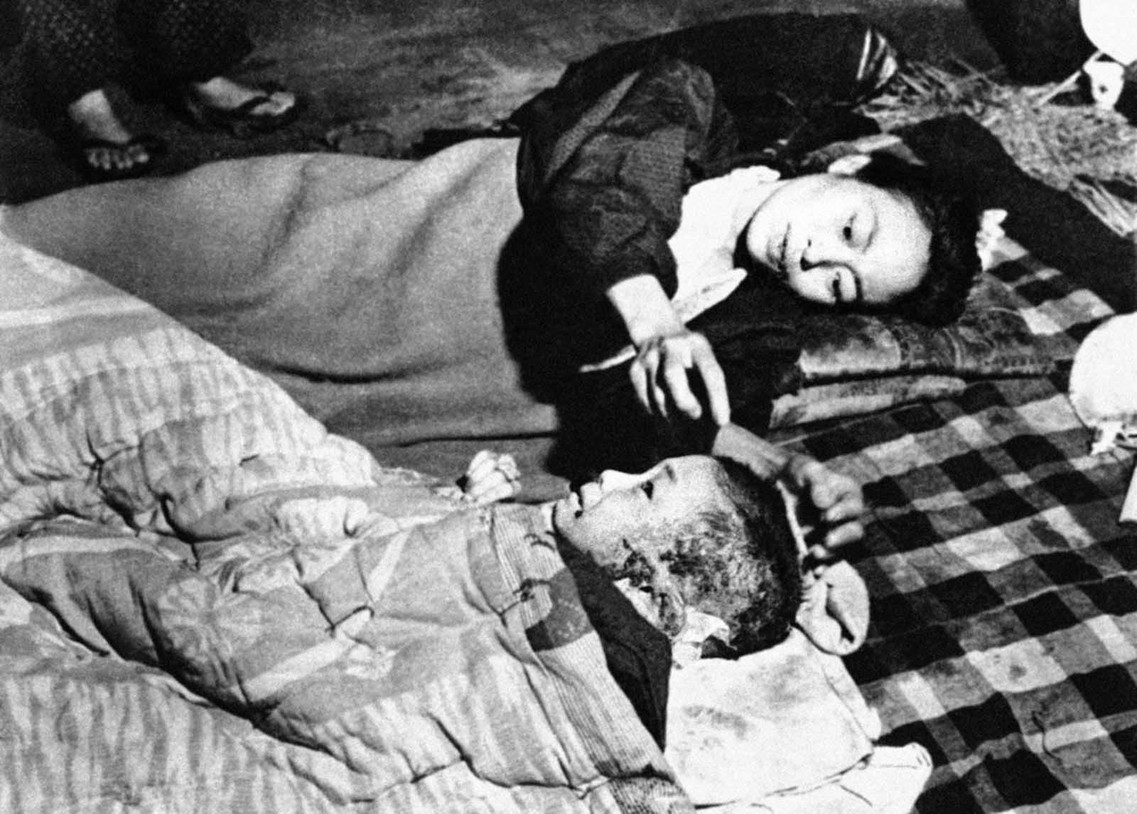 A Japanese woman and her child, casualties in the atomic bombing of Hiroshima, lie on a blanket on the floor of a damaged bank building converted into a hospital and located near the center of the devastated town, on October 6, 1945.