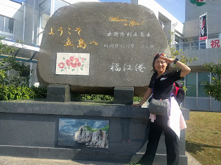 福江港にある「ようこそ!」と書かれた石碑の前に立つ私