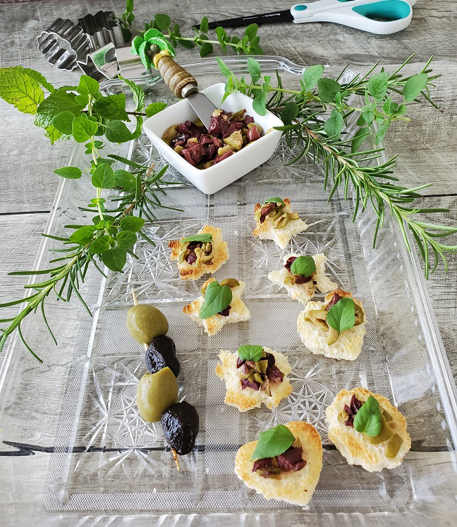 these are mini appetizers cut out by pampered chef cookie cutters and made into garlic bread for an olive topped creative appetizer