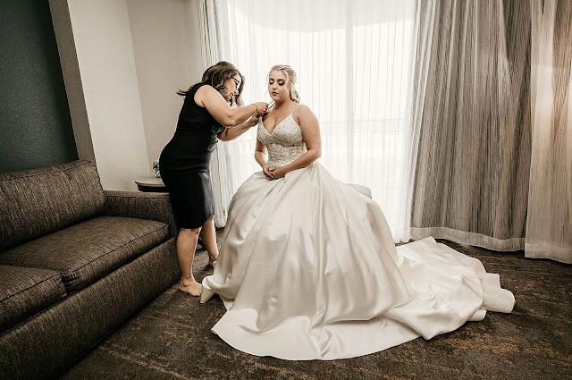 Bride getting help putting on wedding dress